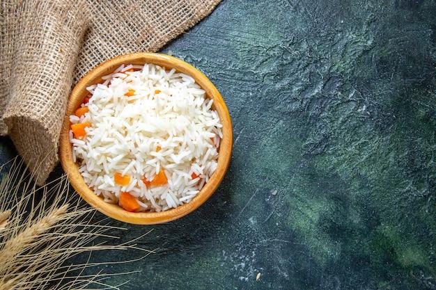 Widok z góry smaczny gotowany ryż w małym talerzu na ciemnym biurku