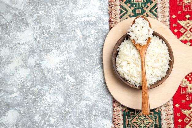 Widok z góry smaczny gotowany ryż wewnątrz brązowego talerza na jasnobiałym