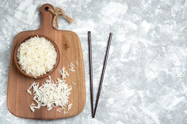 Widok z góry smaczny gotowany ryż wewnątrz brązowy talerz na białym tle