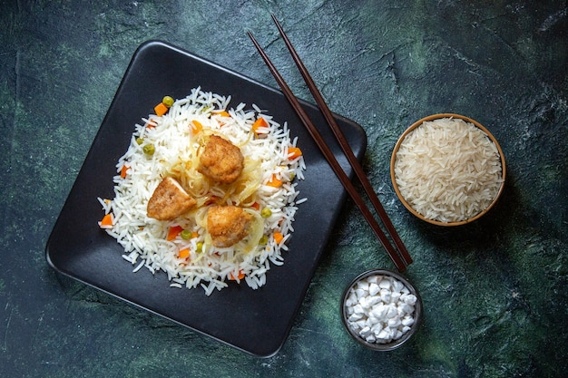Widok z góry smaczny gotowany ryż z fasolą i mięsem wewnątrz talerza na ciemnym biurku