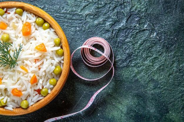 Widok z góry smaczny gotowany ryż z fasolą wewnątrz płyty na ciemnym biurku