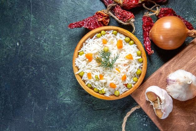 Widok z góry smaczny gotowany ryż z suszoną papryką i czosnkiem na ciemnym biurku