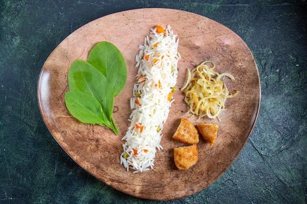 Widok z góry smaczny gotowany ryż z zielonymi liśćmi fasoli i mięsem wewnątrz płyty na ciemnym biurku