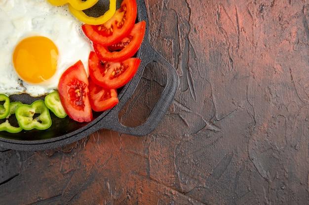Widok z góry smaczny omlet z pokrojoną papryką i pomidorami na ciemnym stole