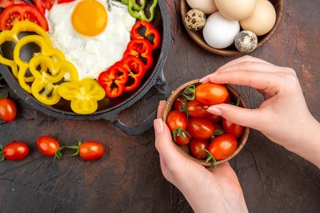 Widok z góry smaczny omlet z pomidorami i pokrojoną papryką na ciemnym stole