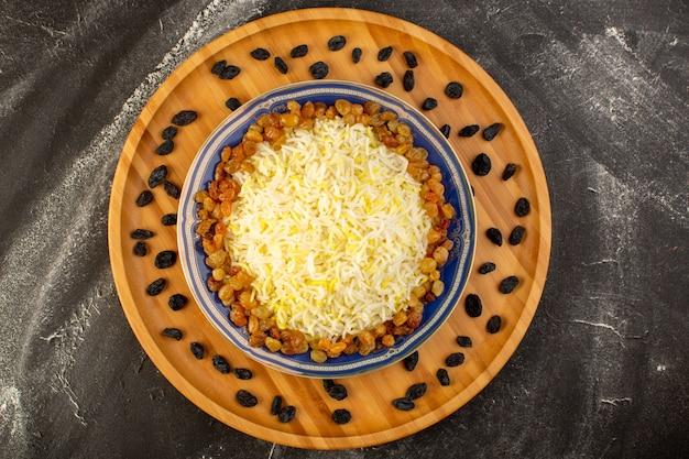 Widok z góry smaczny pilaw z oliwą i suszonymi rodzynkami wewnątrz talerza na ciemnej powierzchni