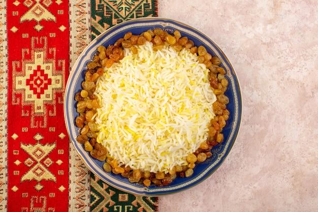 Widok z góry smaczny pilaw z oliwą i suszonymi rodzynkami wewnątrz talerza na różowej powierzchni