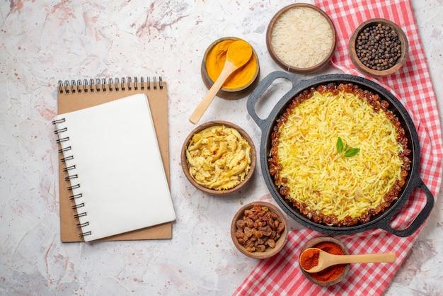Widok z góry smaczny plov w dużej patelni czarny pieprz surowy ryż kurkuma sos z kurczaka suche winogrona czerwona papryka w małych miseczkach zeszyty na stole
