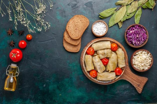 Widok z góry smaczny posiłek mięsny zawijany z kapustą i pomidorami tzw. dolma z oliwą i pieczywem na granatowo