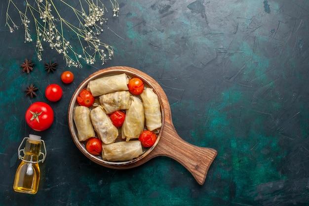 Widok z góry smaczny posiłek mięsny zawijany z kapustą i pomidorami zwany dolma z oliwą z oliwek na granatowym biurku