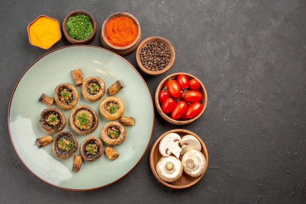 Widok z góry smaczny posiłek z grzybów ze świeżymi pomidorami i przyprawami na ciemnej powierzchni danie obiadowy posiłek gotowania grzyba