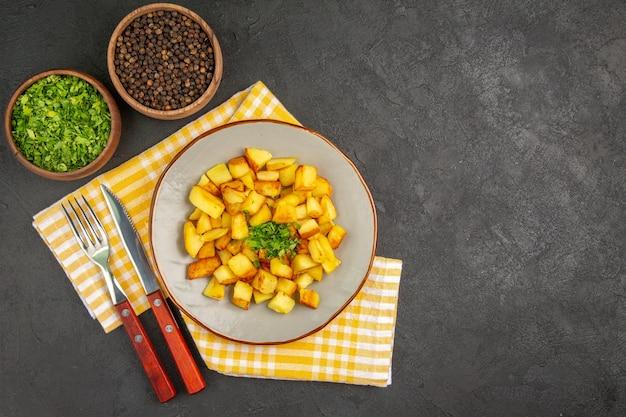 Widok z góry smacznych smażonych ziemniaków wewnątrz talerza na ciemnoszarej powierzchni