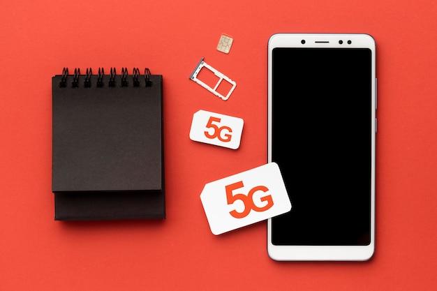 Widok z góry smartfona z kartą sim i notebookiem