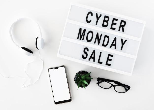 Widok z góry smartfona z okularami i słuchawkami na cyber poniedziałek