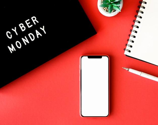 Widok z góry smartfona z rośliną i notatnikiem na cyber poniedziałek