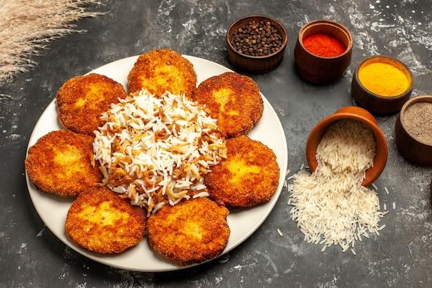Widok z góry smażone kotlety z gotowanym ryżem i przyprawami na ciemnym naczyniu mięsnym