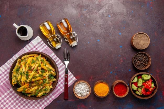 Widok z góry smażone ziemniaki smaczne frytki z zieleniną i olejem na ciemnym biurku