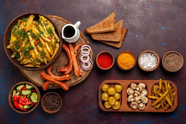 Widok z góry smażone ziemniaki z przyprawami bochenki chleba i różne warzywa na ciemnym biurku