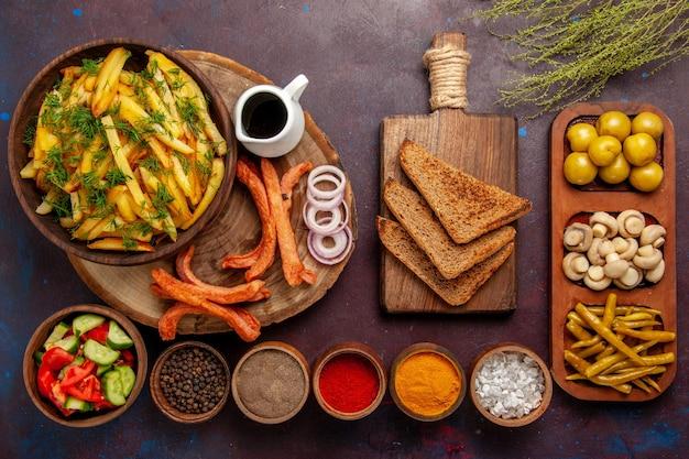 Widok z góry smażone ziemniaki z przyprawami, chleb i różne warzywa na ciemnej powierzchni