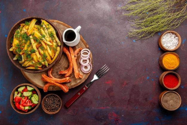 Widok z góry smażone ziemniaki z przyprawami i różnymi warzywami na ciemnej powierzchni