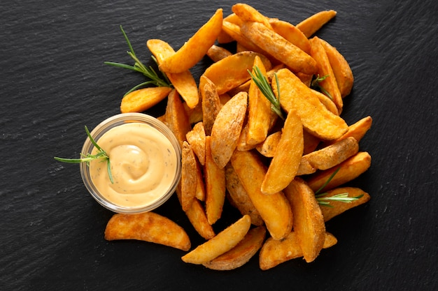 Widok z góry smażone ziemniaki z ziołami i sosem. złote pieczone ziemniaki, szybkie domowe jedzenie.