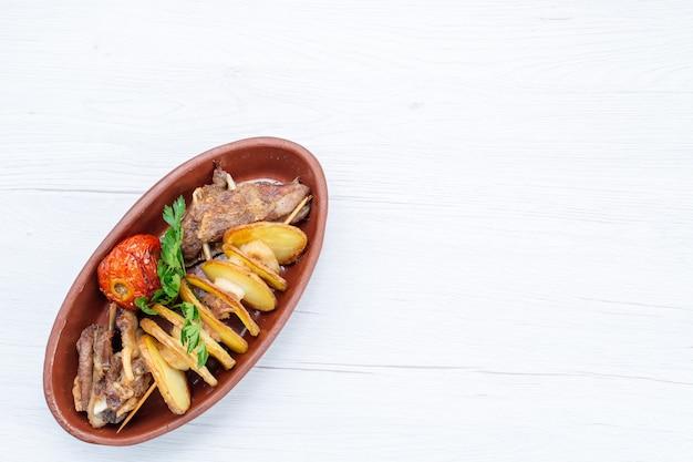Widok z góry smażonego mięsa z zieleniną i pieczonymi śliwkami wewnątrz brązowego talerza na lekkim biurku, kolacja z daniem mięsnym