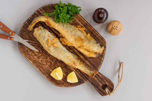 Widok z góry smażonej ryby navaga podawanej na drewnianej desce do krojenia z cytryną, warzywami i zielenią na szarym tle.