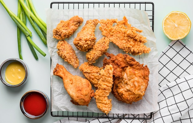 Widok z góry smażony kurczak na tacy z sosami, zieloną cebulą i cytryną