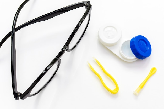 Widok z góry soczewek kontaktowych, pęsety i okularów z aplikatorem na białym. optometria, wzrok poprawny