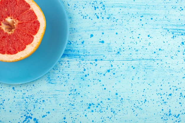 Widok z góry soczystego grejpfruta pokrojonego w plastry na niebieskim talerzu i jasnoniebieskiej podłodze