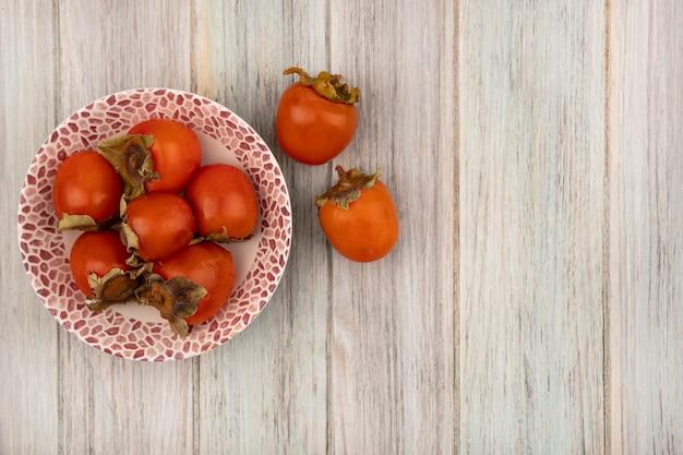 Widok z góry soczystych miękkich persymonów na misce z persimmons odizolowanymi na szarej drewnianej ścianie z miejscem na kopię
