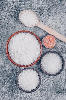 Widok z góry soli w szkle, miseczkach i drewnianą łyżką soli himalajskiej