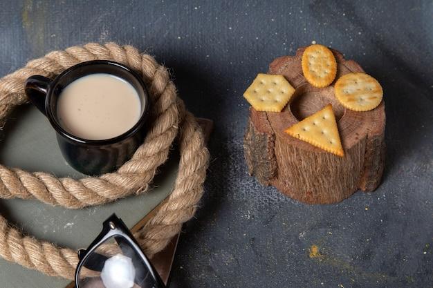 Widok z góry solone chipsy z czarną filiżanką mleka na ciemnym biurku jedzenie posiłek śniadanie przekąska napój