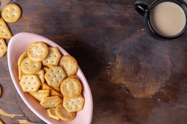 Widok z góry solone smaczne chipsy z czarną filiżanką mleka na drewnianym tle jedzenie śniadanie posiłek przekąska