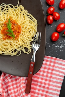 Widok z góry spaghetti z sosem na talerzu widelec pomidorki koktajlowe na czarnym stole