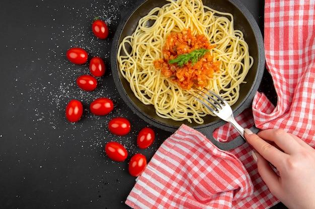 Widok z góry spaghetti z sosem w widelcu patelni w kobiecej dłoni pomidorkami koktajlowymi na czarnym stole wolne miejsce