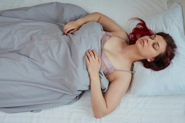 Widok z góry śpiącej kobiety z rudymi włosami, leżącej na plecach w łóżku z zamkniętymi oczami.