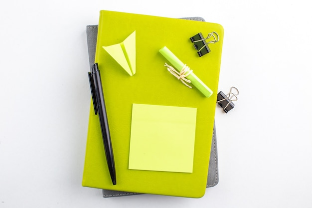 Widok z góry spinacze do karteczek samoprzylepnych na notatnikach czarny długopis papierowy samolot na białym tle
