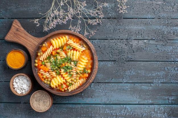 Widok z góry spiralna zupa z makaronem pyszny posiłek z różnymi przyprawami na ciemnym biurku zupa kolory włoska kuchnia makaronowa