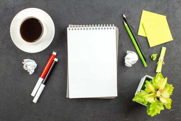 Widok z góry spiralny notatnik czerwone i czarne markery zielone i czarne ołówki filiżanka herbaty karteczki samoprzylepne na czarno