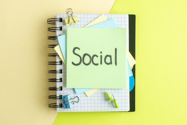 Widok z góry społeczna pisemna uwaga na naklejkach z notatnikiem na żółto-zielonym tle kolegium praca wynagrodzenie biuro zeszyt kolor szkoła biznes pieniądze zdjęcie
