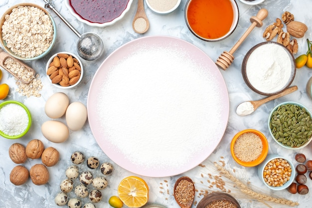 Widok z góry sproszkowana mąka na talerzu drewniana łyżka migdały jajka miski z dżemem miód sezam kukurydza i inne dodatki