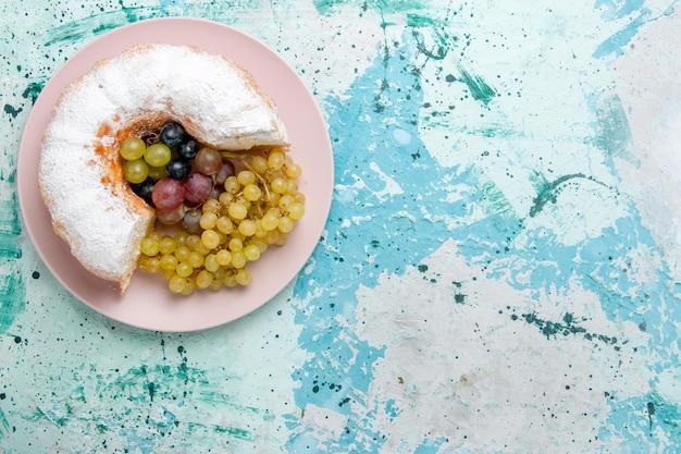 Widok z góry sproszkowane ciasto pokrojone pyszne ze świeżymi winogronami na jasnoniebieskiej powierzchni