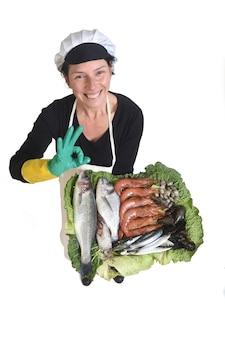 Widok z góry sprzedawcy ryb pokazującego talerz z rybami i owocami morza, wykonującego ręką znak ok i patrzącego w kamerę