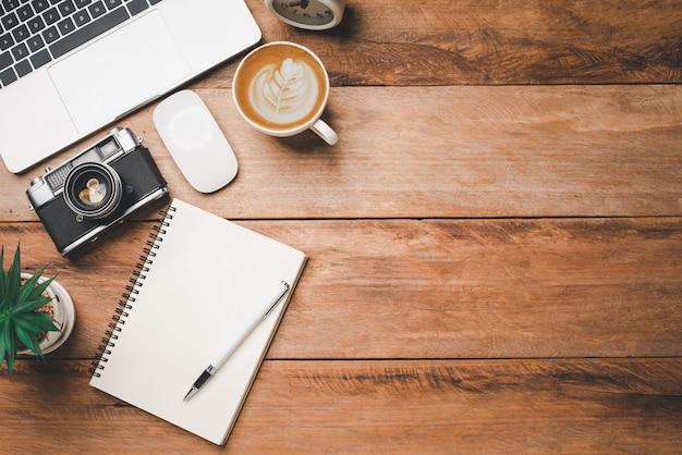 Widok z góry sprzęt biurowy, w tym laptop, telefon komórkowy, mysz, notebook, filiżanka kawy na drewnianej podłodze