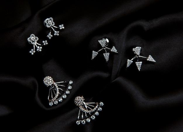 Widok z góry srebrnych kolczyków z kryształem swarovskiego z ćwiekami na czarnej ścianie