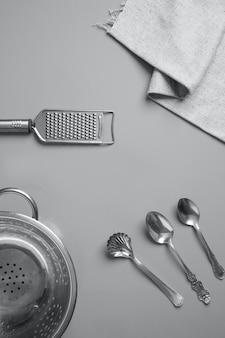 Widok z góry srebrnych przyborów kuchennych i szarej serwetki na szaro
