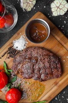 Widok z góry stek z pomidorem i pikantnym sosem w desce stekowej