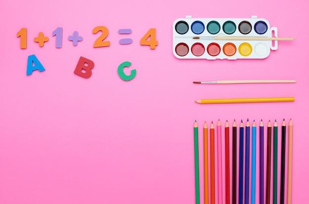 Widok z góry stołu dziecka, kompozycja pędzla, litery, numery, kredki, gumka, inna linia na różowym tle