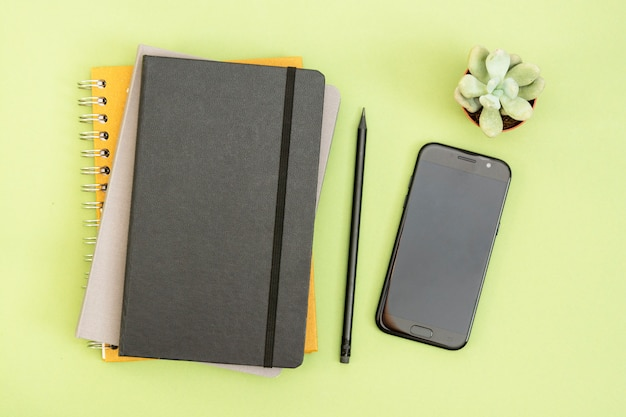 Widok z góry stołu roboczego. czarny zamknięty notatnik, filiżanka kawy i smartfon. skopiuj miejsce na tekst. zaprojektuj makietę.